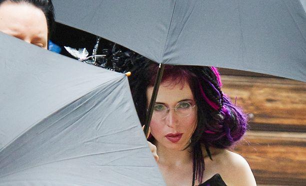 Turvamiehet saattelivat morsiamen autoon sateenvarjoilla suojaten.