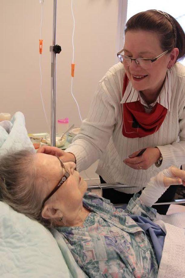 Riitta Järvinen auttaa 94-vuotiasta äitiään Terttu Ylisuvantoa syömään sairaalassa.