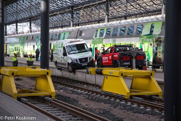 Väki ihmettelee autoa erikoisessa paikassa Helsingin päärautatieasemalla.