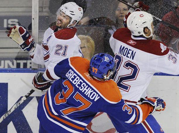 Kuvatoimiston tietojen mukaan tässä Montrealin Travis Moen niittaa joukkuetoveriaan Brian Ginotaaa Edmontonin Denis Grebeshkov pääsee viilettämään ohi. Kieltämättä Giontan ilme on tuskainen.