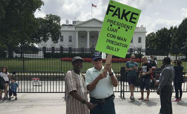 Oikeanpuolinen mies Mike Dirby protestoi Valkoisen talon edustalla ennen presidenttien tapaamista.