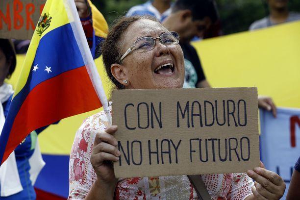 """Nainen osoitti mieltään hallitusta vastaan elokuussa Valenciassa Venezuelassa. Espanjankielisessä kyltissä lukee """"Maduron kanssa ei ole tulevaisuutta""""."""