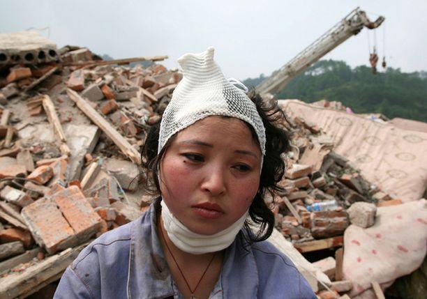 Maanjäristyksestä selvinnyt istuu sortuneiden talojen raunioilla Sichuanin maakunnassa.