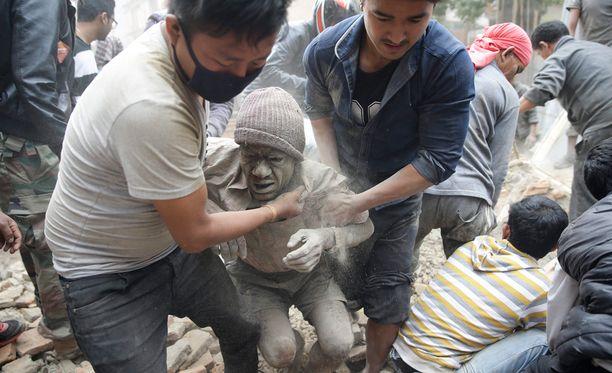 Paikalliset auttoivat romahtaneen talon raunoihin jäänyttä miestä Nepalin pääkaupungissa Kathmandussa.