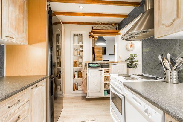 Keittiöön on onnistuttu sijoittamaan jopa astianpesukone. Lisää säilytys ja laskutilaa on luotu seinään upotetuilla hyllyillä ja pienellä saarekkeella. Myös katonraja on hyödynnetty fiksusti: sinne on laitettu hylly viinilaseja varten.