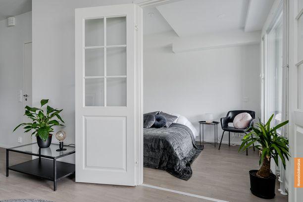 Makuuhuone yhdistyy asunnon pohjassa kauniisti olohuoneeseen, mutta ovilla saa halutessa yksityisyyttä.