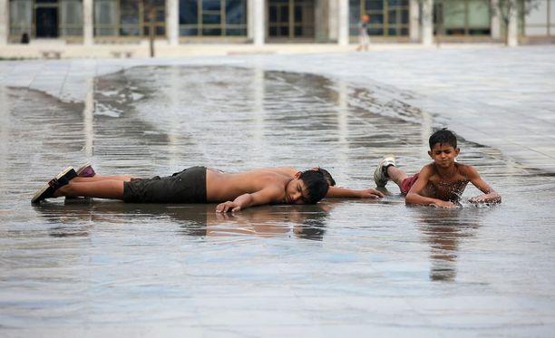 Lapset leikkivät suihkulähteessä Albaniassa.