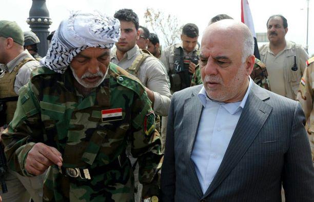 Irakin hallinnon julkisuuteen antama kuva pääministeri Haider al-Abadista (oikealla) vapautetussa Tikritissä yhdessä vapaaehtoisina taisteluihin osallistuneiden shiiamuslimien kanssa.