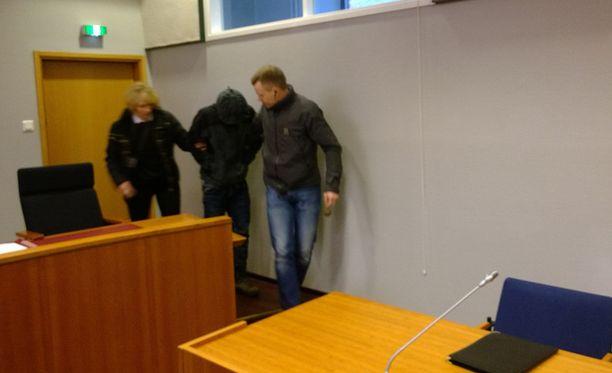 Toinen epäillyistä saapui käräjäoikeuteen kasvot peitettynä.