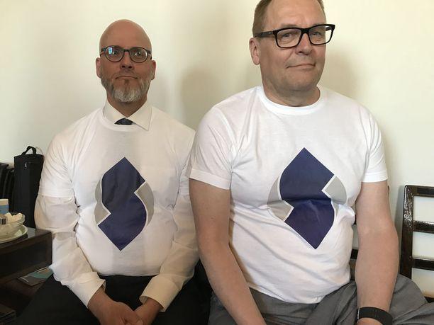 Tältä näytti Sinisen tulevaisuuden tuore logo puolueen vaalipäällikkö Pekka Sinisalon ja puoluesihteeri Matti Torvisen päällä.