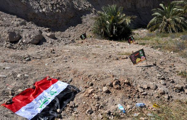 Irakin lippu lepää vuosi joukkomurhan jälkeen löytyneen joukkohaudan päällä.