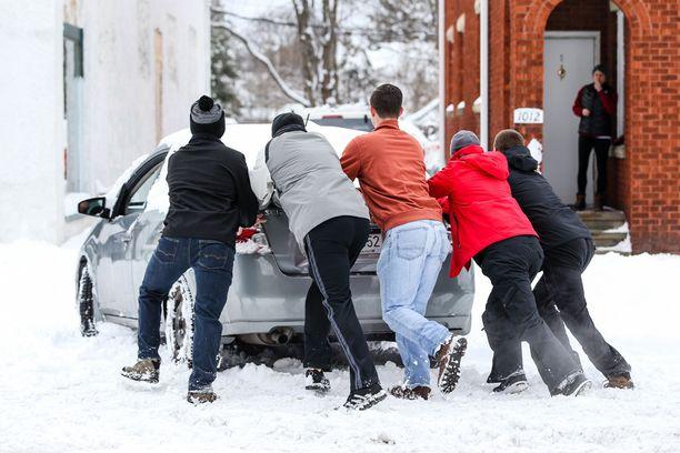 Ystäväporukka työntää lumeen juuttunutta autoa.