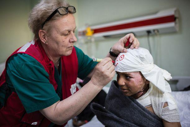 11-vuotias Yasser oli kotona Mosulissa perheensä kanssa, kun ohjus syöksyi katon läpi. Lääkäreiden piti leikata pois Yasserin pitkät hiukset, ja hän häpesi hiuksettomuuttaan. Kati Partanen lohdutti poikaa askartelemalla huivin ja koristelemalla sen hymynaamalla.