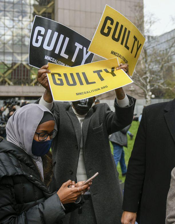 Minneapolisin oikeustalon edustalla väkijoukosta  nousee kyltit jokaista Chauvinin saamaa kolmea syytettä symbolisoimaan.