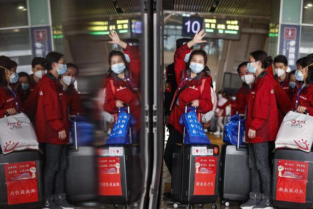 Hubein maakuntaan lähetetyt lääkärit vilkuttivat Wuhanin asemalla kotimatkan alkamisen merkiksi.