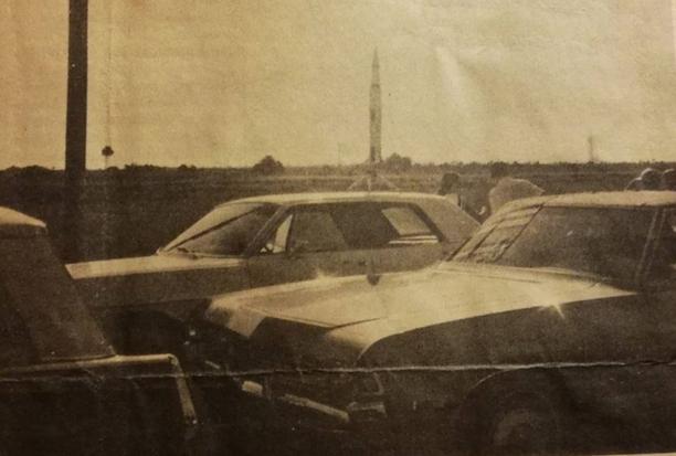 Eero Kavastolla on todisteena tapahtuneesta valokuva. Etualalla näkyy auton katolle kiinnitetty pienoismalli, otoksen oikeassa reunassa häämöttää oikea Saturnus 5.