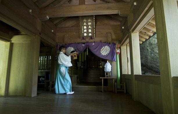 Sintolaispappi suorittamassa uskonnollisia menoja yhdessä saaren pyhäköistä.