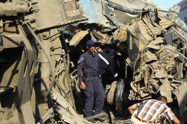 Egyptin turvallisuusviranomaiset tutkivat törmäyksessä tuhoutuneita junia.