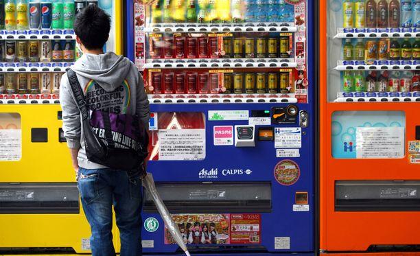 Nuori japanilainen tutustui juoma-automaatin tarjontaan Tokiossa.
