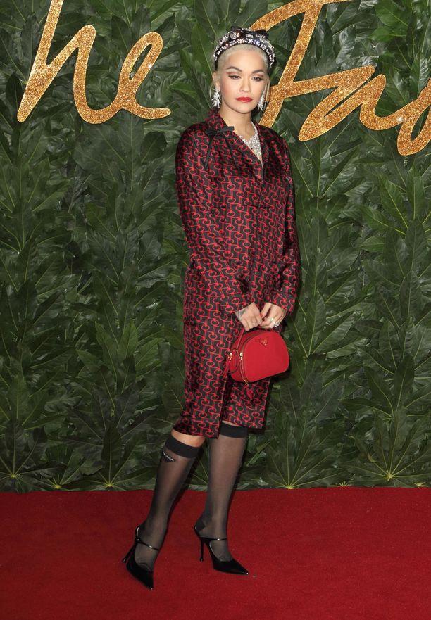 Erilainen Rita Ora Fashion Awards 2018 -gaalassa Lontoossa! Tässä asussa on 1950-luvun henkeä läpinäkyvine polvisukkineen. Takin ja mekon yhdistelmä voisi näyttää monella mummomaiselta, mutta Oralle saa senkin näyttämään seksikkäältä.
