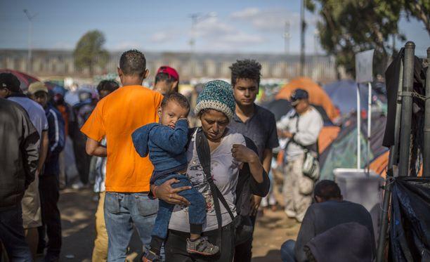 Tijuana, Meksiko perjantaina 23. marraskuuta. Karavaanin mukana saapunut äiti ja poika odottelevat asiansa käsittelyä telttakylässä. Alueella on arviolta 4000 Keski-Amerikasta lähtenyttä ja Yhdysvaltoihin pyrkivää siirtolaista. Moni heistä toivoo saavansa turvapaikan.