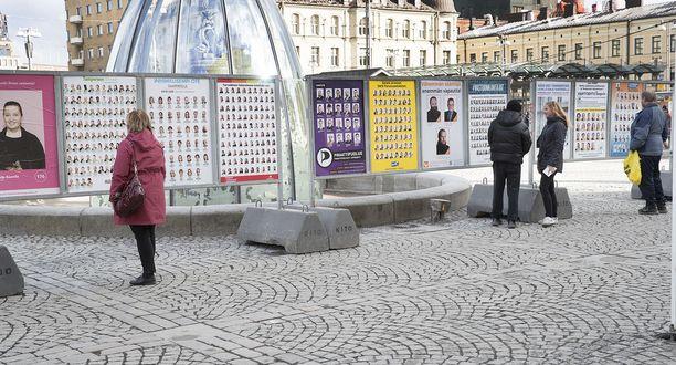 Tamperelaiset tutkivat kuntavaalien julisteita kaupungin keskustorilla.