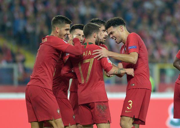 Portugalin pelaajat kokoontuvat juhlimaan Rafa Silvan (numero 17) juonimaa 2-1-maalia.