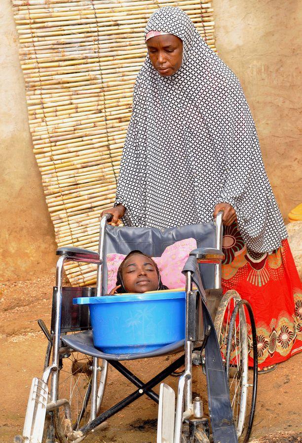 Elämä helpottui, kun Rahma sai lahjoituksena pyörätuolin. Kuvassa myös hänen äitinsä Fadi.