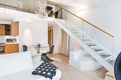Makuuparvi, isot ikkunat ja parveke lisäävät pienen ullakkoasunnon tilantuntua Helsingin Ullanlinnassa.