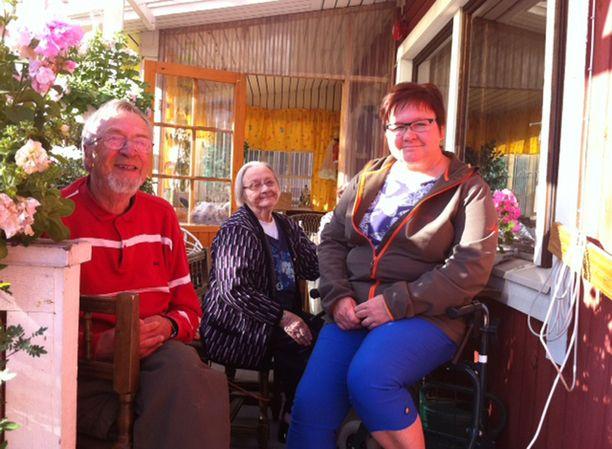 Anna-Liisa Kemppainen Martan ja Sepon kanssa hoivakodin terassilla.