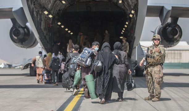 Ihmisiä nousemassa USA:n evakuointikoneeseen.