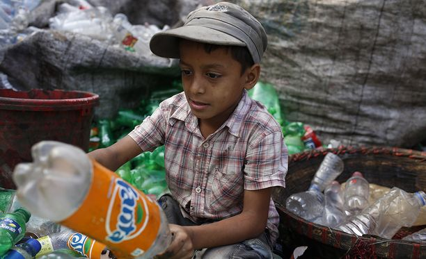Tämä poika lajittelee muovipulloja uusiokäyttöön Bangladeshissa.