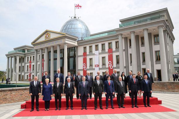 Vieraat ja isännät yhteiskuvassa Georgian presidentin linnan edustalla Tbilisissaä.