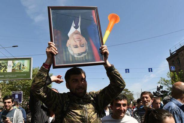 Mielenosoittaja pitelee pääministeri ja ex-presidentti Sarkisianin kuvaa ylösalaisin.