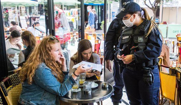 Poliisit tarkastavat asiakkaiden koronapasseja kahvilassa Pariisissa.