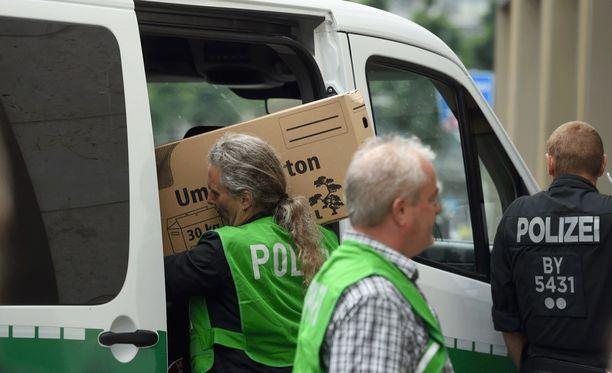 Poliisin tutkijat kantoivat laatikoittain todisteita ulos perheen asunnosta.