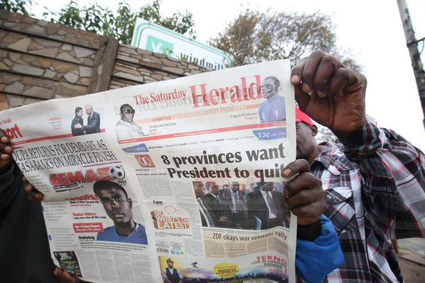 Zimbabwelaismiehet lukivat lauantaina lehteä, jossa kerrottiin Mugaben vastaisista mielenosoituksista ja erovaatimuksista.