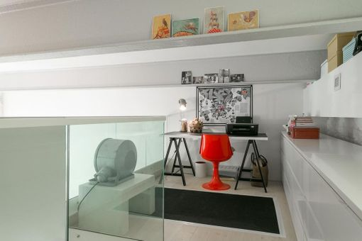 Loft-yksiössä työ- ja säilytystilaa on rakennettu parvelle. Punainen Tulppaani-tuoli on ihana yksityiskohta muuten vaaleassa sistuksessa.