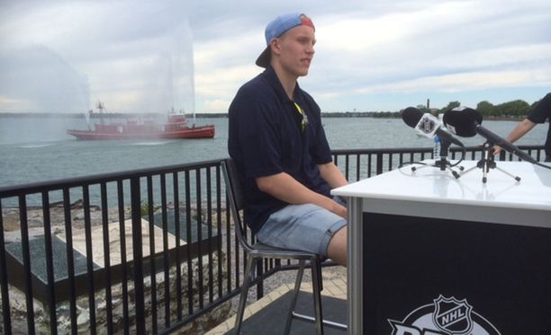 Patrik Laine vastaili median kysymyksiin eilen Erie-järven rannalla palontorjunta-aluksen ruiskutellessa vettä taustalla.