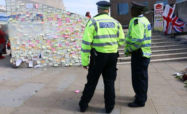 Poliisit vartioivat tapahtumapaikkaa, jonne on tuotu runsaasti surunvalitteluja iskun uhreille.