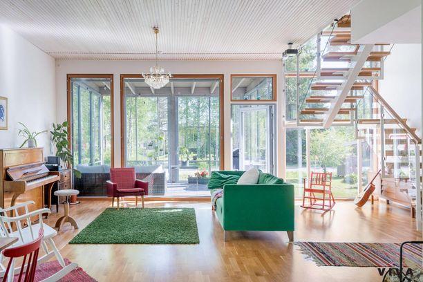 Olohuoneen valoisuus lyö ällikällä. Tammiparketti, ikkunakehykset ja portaikon askelmat on jätetty kauniisti puunsävyiseksi.
