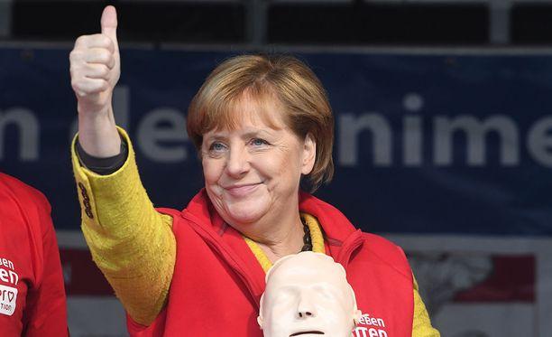 Saksan liittokansleri Angela Merkelin kristillisdemokraatit (CDU/CSU) on pitämässä maan suurimman puolueen paikan, mielipidemittaukset ennustavat. Kuvassa Merkel pitää vasemmalla kädellään kiinni elvytysnukesta, jonka avulla hän muiden mukana kertasi elvytysohjeita kampanjatilaisuudessaan.