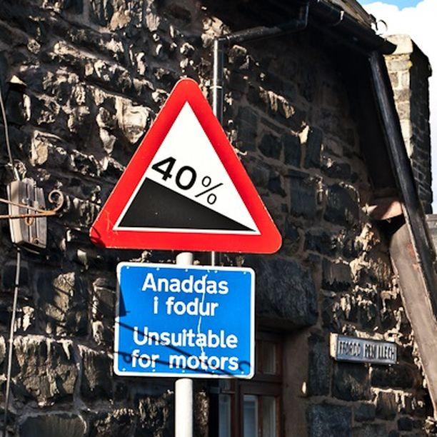Varoitusmerkki Ffordd Pen Llech -kadulla. Siinä jyrkkyysastetta on vielä pyöristetty ylöspäin.
