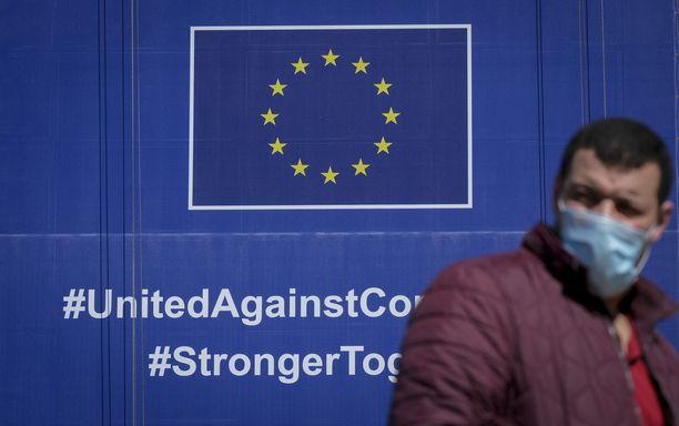 Kasvomaskiin pukeutunut mies kävelee Euroopan komission kyltin ohi toukokuussa 2020. Kuvituskuva.