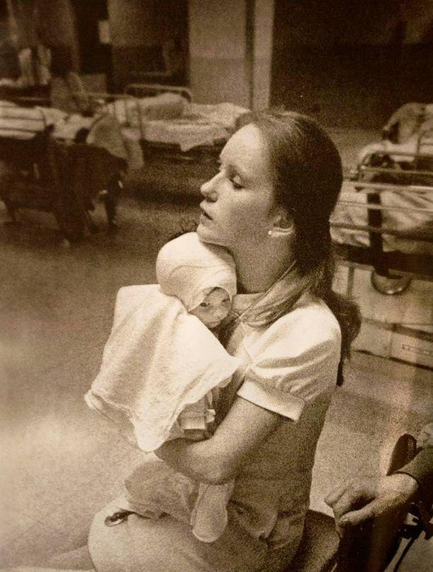 Vuonna 1977 otetuissa mustavalkokuvissa hoitaja ja vauva muistuttavat ikonista asetelmaa.