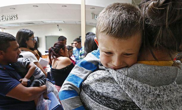 Siirtolaisperheitä odottaa lähtöä bussiasemalla McAllenissa Teksasissa.