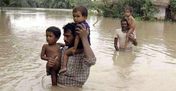 Kyläläiset vaeltavat tulvaveden läpi Biharin osavaltiossa Intiassa.