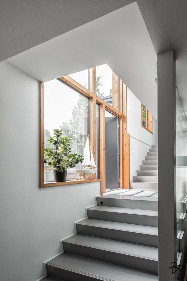 Harmaat betoniportaat ja vaaleasta puusta tehdyt ikkunanpuitteet ovat trendikäs väri- ja materiaaliyhdistelmä.