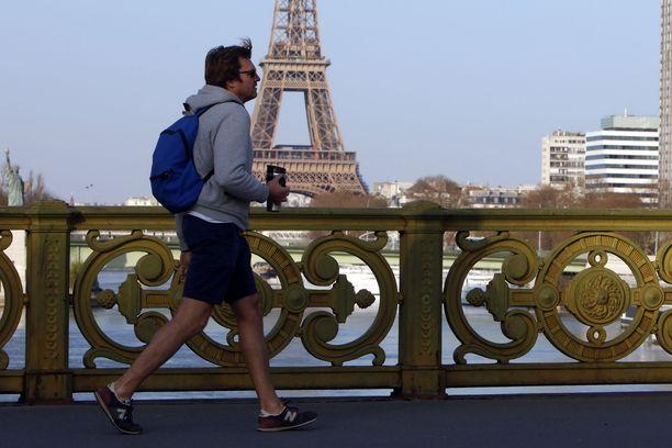 Yksinäinen lenkkeilijä Eiffel-tornin edustalla Mirabeau-sillalla.