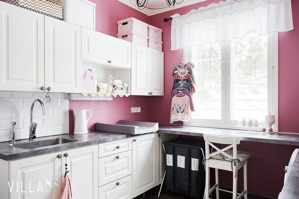 Moni suosii kodinhoitohuoneissa valkoista väriä, koska se viestii puhtaudesta ja avartaa pientä tilaa. Tässä kodinhoitohuoneessa on seinät maalattu rohkeasti pinkiksi - ja se todella kannattaa!